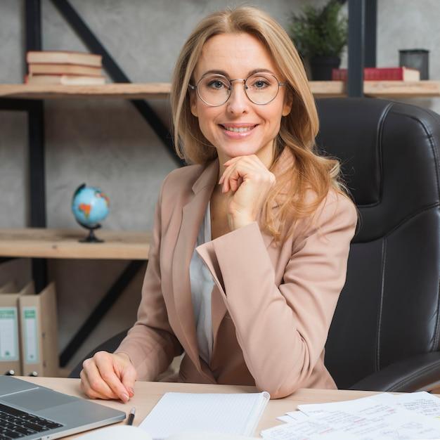 職場で椅子に座っている自信を持って若いブロンドの実業家の肖像画 無料写真