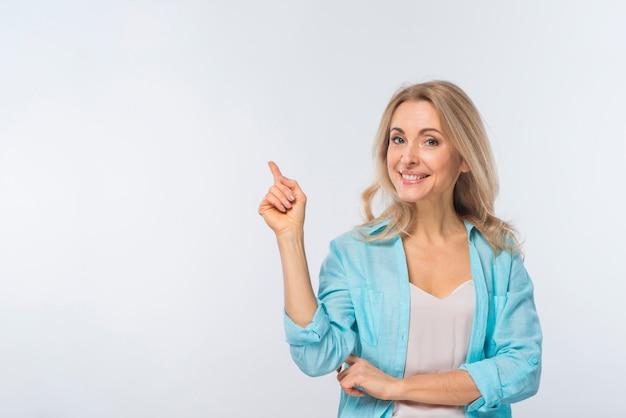 白い背景に対して彼女の指を指している若い女性の笑みを浮かべてください。 無料写真