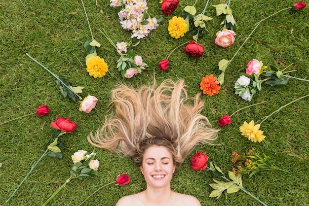 花の間草の上に横たわる陽気な女性 無料写真
