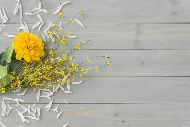 灰色の木製の机の上の黄色い花 無料写真