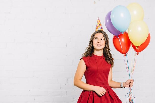 Улыбающийся портрет девушки с разноцветными шарами в руках Бесплатные Фотографии