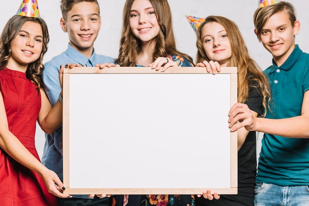テキストを書くための白い空白のフレームを保持しているパーティーハットを着て笑顔の友人のグループ 無料写真