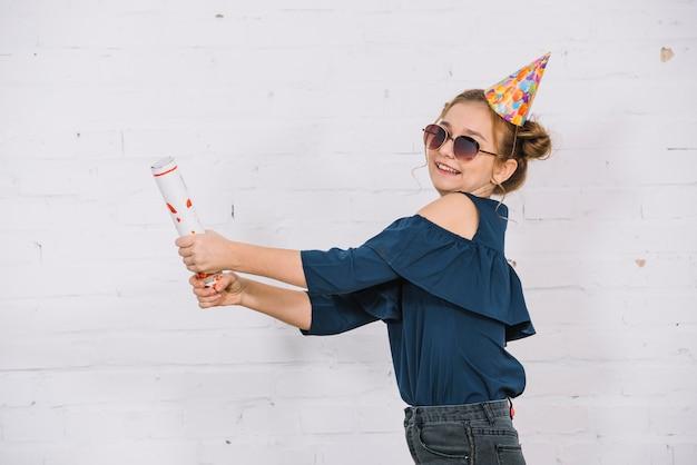 Улыбающаяся девочка-подросток, отпуская вечеринку поппер, стоя перед белой стеной Бесплатные Фотографии