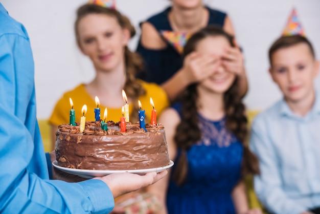 彼女の友人によって覆われた目で誕生日の女の子にチョコレートケーキをもたらす男の子の手のクローズアップ 無料写真