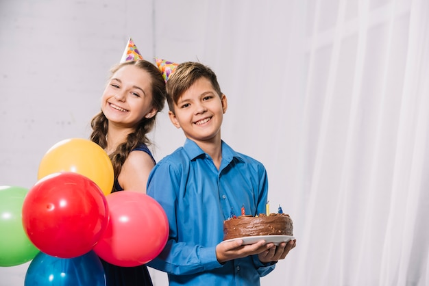 男の子と女の子のカラフルな風船と皿の上のケーキを保持の肖像画 無料写真