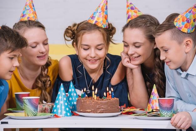 キャンドルで照らされた誕生日ケーキを見ている友人のグループ 無料写真
