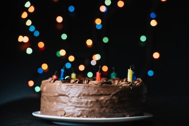 キラキラボケ味に対するチョコレートケーキは黒の背景をライトします。 無料写真