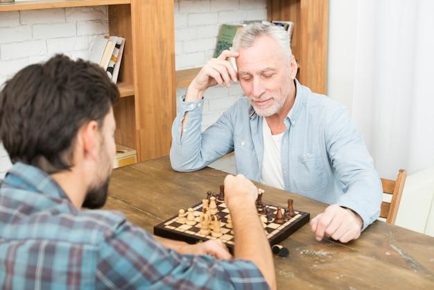 物思いにふける老人男性と本棚の近くのテーブルでチェスをする若い男 無料写真