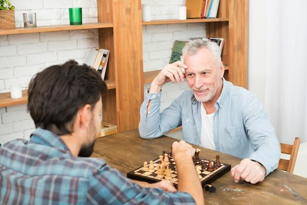 本棚の近くのテーブルでチェスをしている老人と若い男 無料写真