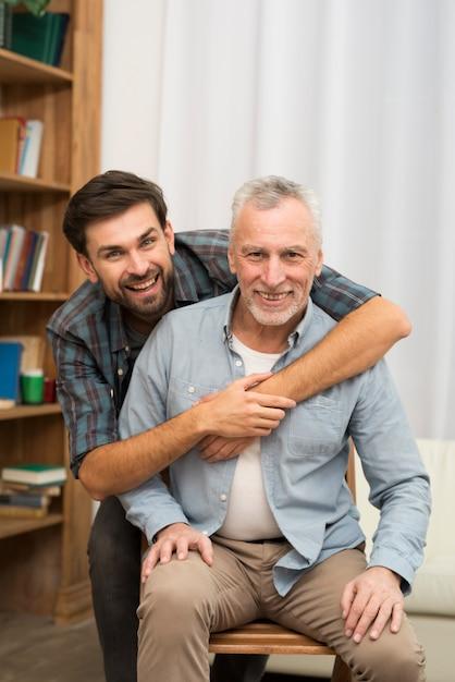 椅子に老人を抱いて若い幸せな男 無料写真