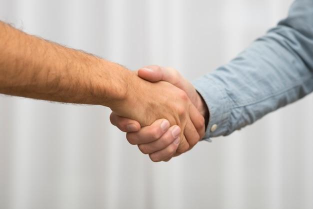 Мужчины пожимают друг другу руки в комнате Бесплатные Фотографии
