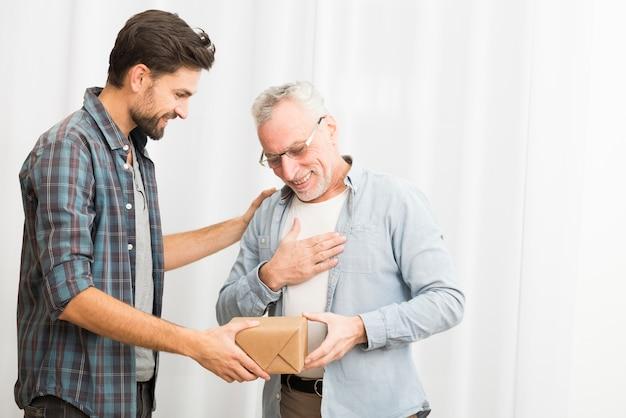 Молодой парень дарит подарок пожилому счастливому мужчине Бесплатные Фотографии