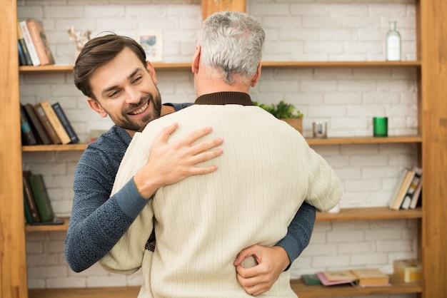本棚の近くの老人とハグする若い幸せな男 無料写真