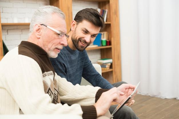 老人と若い被告人にタブレットを使用して 無料写真