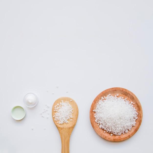 白い背景の上の純粋な岩塩と保湿クリーム 無料写真