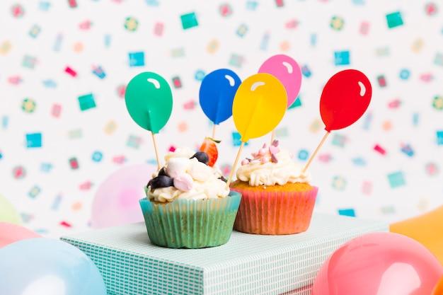 ブルーボックスにバルーントッパーのカップケーキ 無料写真