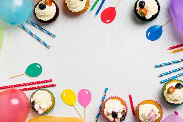 気球とテーブルの上のろうそくのカップケーキ 無料写真