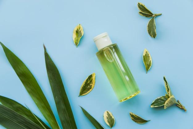 青の背景に緑の葉を持つ緑のスプレーボトルの俯瞰 無料写真