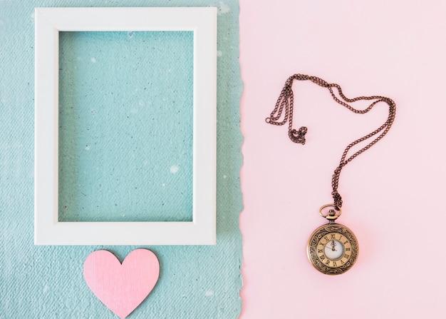 古い懐中時計の近くの青い紙の上のフォトフレームと飾りの心 無料写真