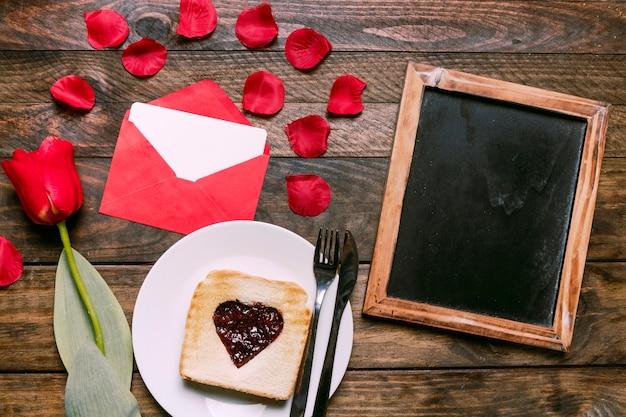 ジャムとカトラリーの花、花びら、手紙とフォトフレームの近くの皿にトースト 無料写真