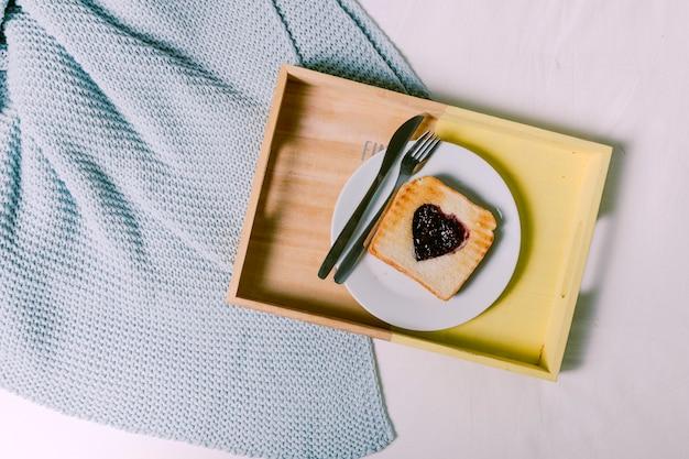 ベッドの上のハートの形のジャム付きトーストトレイ 無料写真