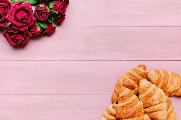 テーブルの上の赤いバラのブーケとクロワッサン 無料写真