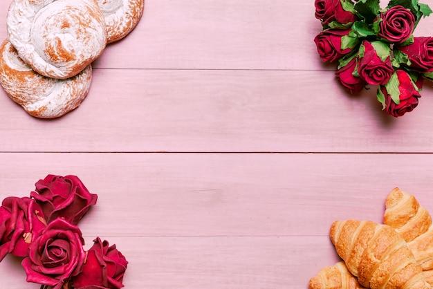 赤いバラの花束とパンのクロワッサン 無料写真