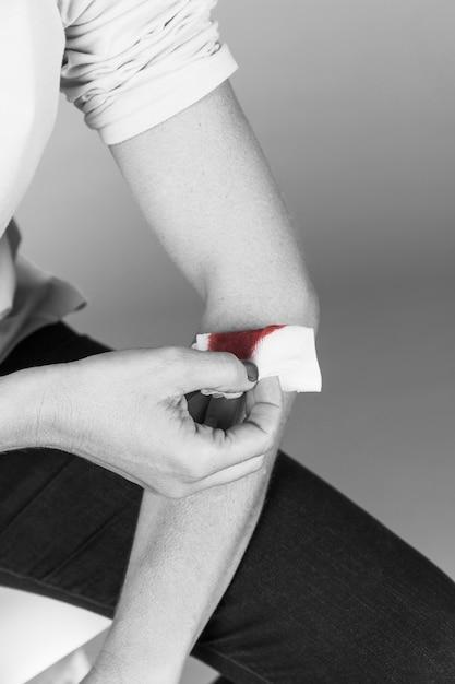 出血の手首に医療包帯を持っている女性の手 無料写真