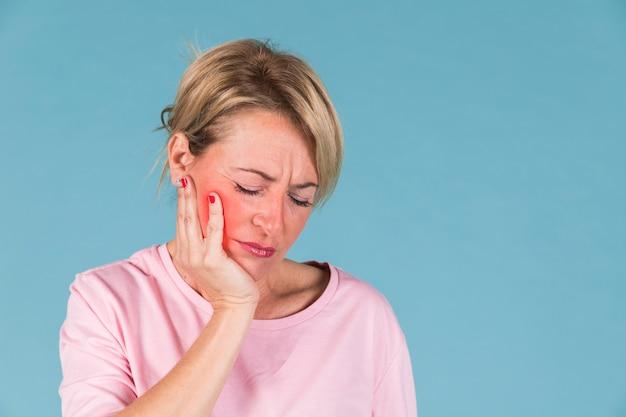 青色の背景の前に歯痛を持つ病気の女性のクローズアップ 無料写真