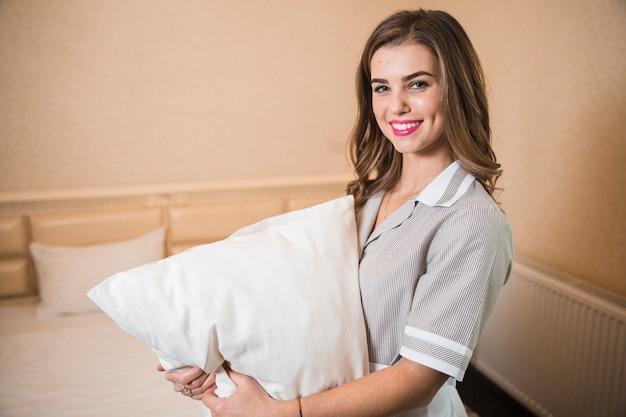 柔らかい白い枕を手で押し、微笑の女中の肖像 無料写真