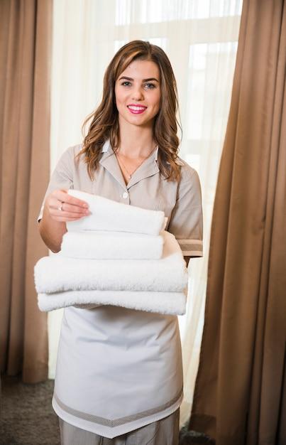 部屋で新鮮なきれいなタオルのスタックを保持している笑顔の若いホテルメイドの肖像画 無料写真