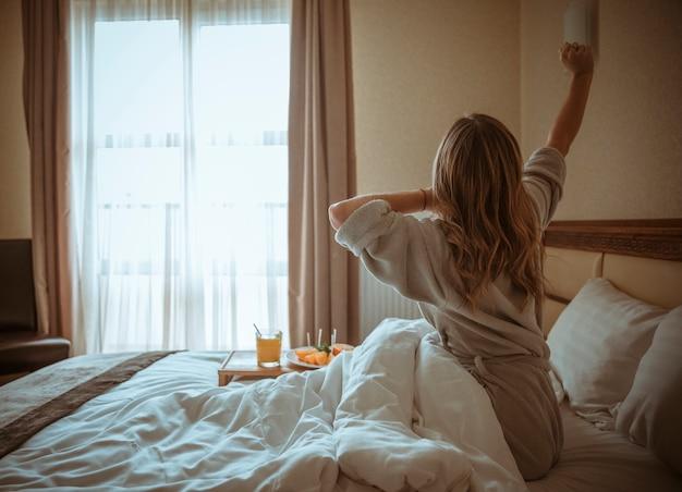 Молодая женщина, сидя на кровати, протягивая руку с завтраком на столе Бесплатные Фотографии