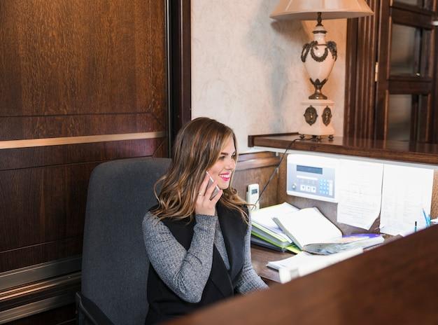 携帯電話で話している陽気な自信を持って若い女性ホテル受付係 無料写真