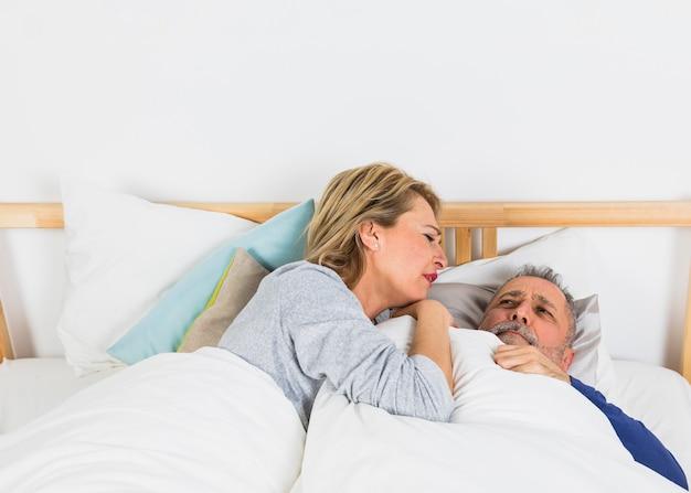 ベッドの上の羽毛布団で悲しい男の近くに横たわっている高齢者の女性 無料写真