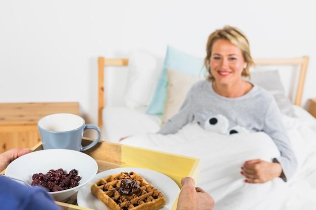 ベッドの上の羽毛布団で高齢者の笑顔の女性の近くの朝食を持つ男 無料写真