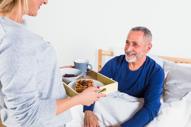ベッドの上の羽毛布団で笑みを浮かべて男に朝食を与える高齢者の女性 無料写真