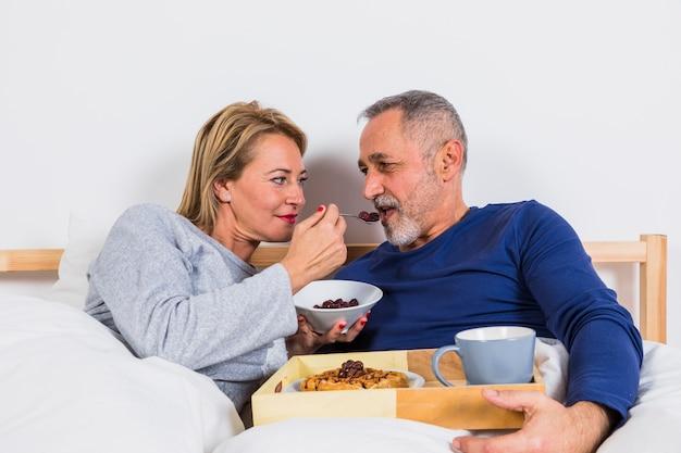 ベッドのトレイ上の朝食近くの羽毛布団の男に果実を与える高齢者の女性 無料写真