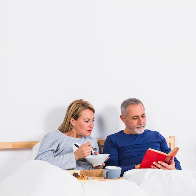 ベッドのトレイ上の朝食の近く布団で本を持つ男の近くにボウルを持つ高齢者の女性 無料写真