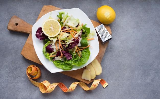 測定テープと木の板に野菜のサラダ 無料写真