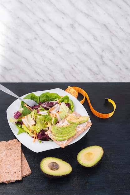 ぱりっとしたパンにグリーンアボカドの野菜サラダ 無料写真