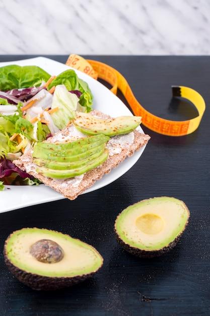 テーブルの上のぱりっとしたパンのアボカドと野菜のサラダ 無料写真