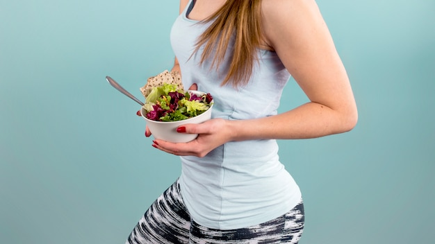 手で野菜のサラダと大きなボウルを保持している女性 無料写真