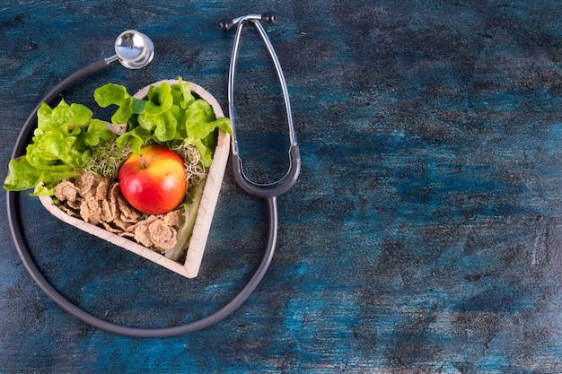 Яблоко с салатом и хлопьями в деревянном сердечке Бесплатные Фотографии