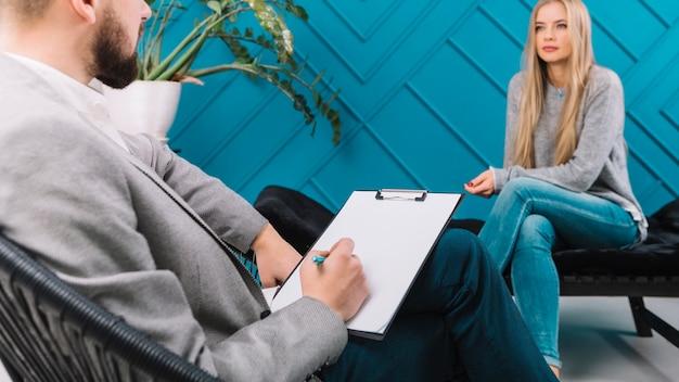 心理学者の彼のメスの患者との会談中にペンでクリップボードにメモを書く 無料写真