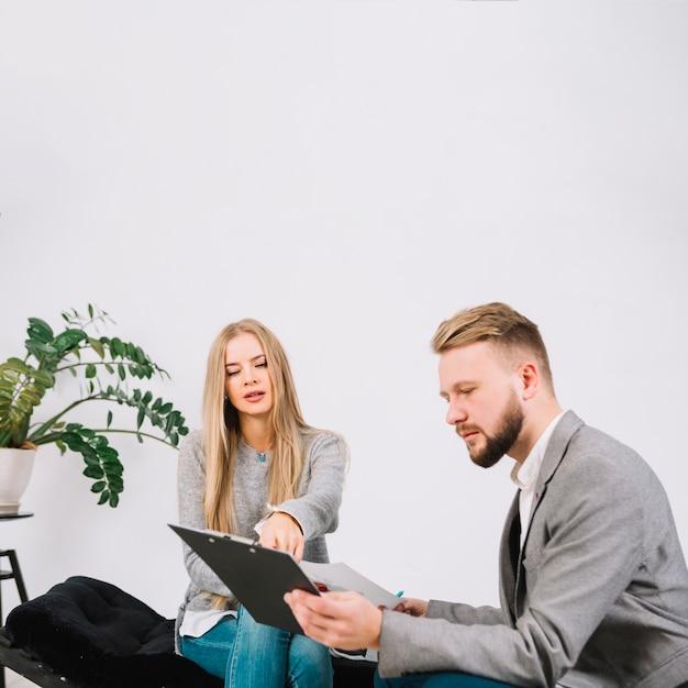 心理学者と結果を議論するソファに座って美しい若い女性 無料写真