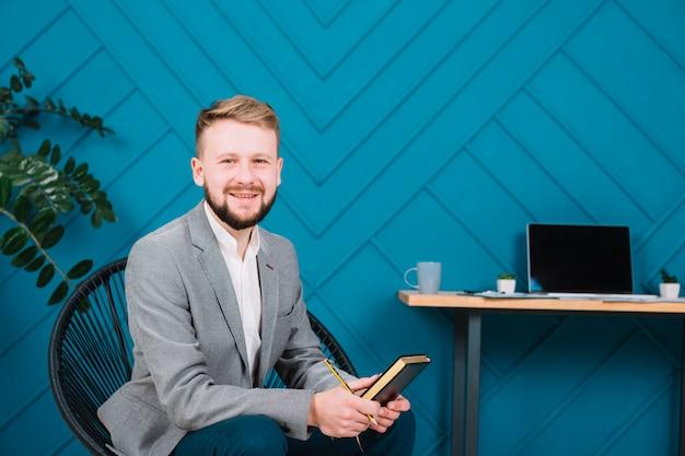 日記と鉛筆を手に持って椅子に座っている若い男性心理学者の肖像画を笑顔 無料写真