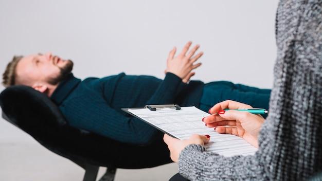治療セッションで医療フォームに記入するクライアントを持つ女性心理学者 無料写真