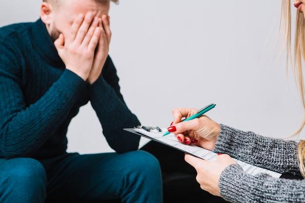 メモを取って男性の落ち込んでいるクライアントと女性心理学者のクローズアップ 無料写真