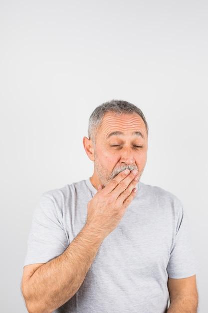口を覆っているあくびの老人 無料写真