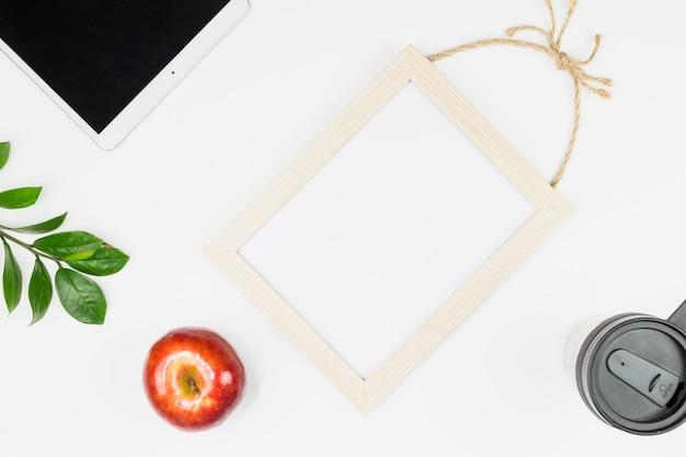 リンゴ、植物の小枝、カップ、フォトフレームの近くにタブレットします。 無料写真